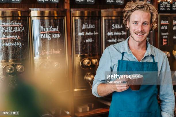 Portrait of smiling coffee roaster in his shop drinking cup of coffee