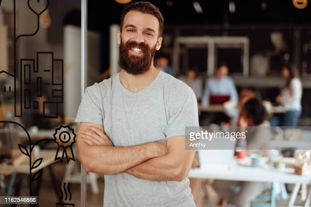 portrait of smiling confident businessman in busy office - 20 29 years stock pictures, royalty-free photos & images