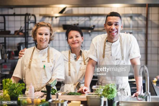 portrait of smiling confident chefs standing at kitchen in restaurant - food service occupation stock pictures, royalty-free photos & images