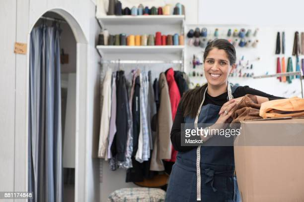 Portrait of smiling confident mature female owner standing by cardboard box at Laundromat