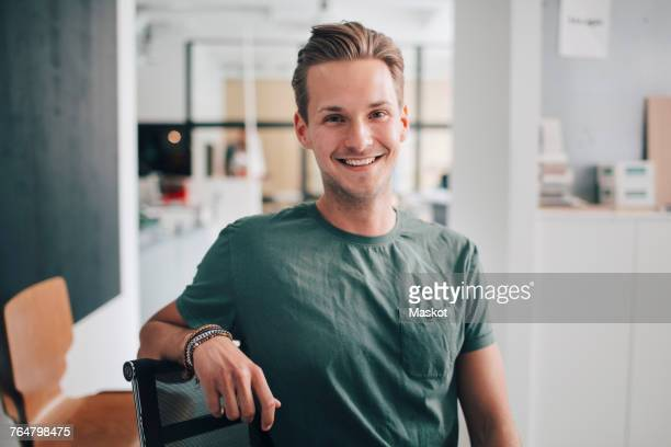 portrait of smiling confident young businessman sitting at office - jonge mannen stockfoto's en -beelden