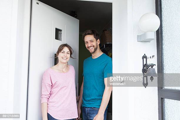 Portrait of smiling couple at front door