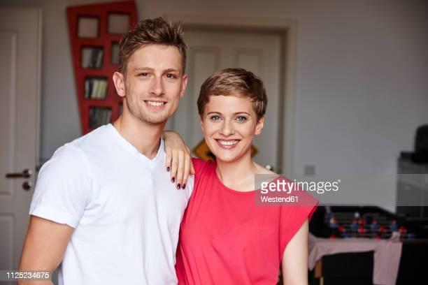 portrait of smiling couple at home - hand auf der schulter stock-fotos und bilder