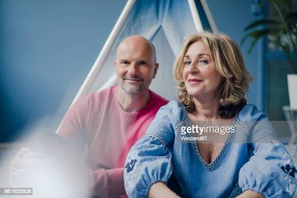 portrait of smiling couple at teepee indoors - jung geblieben stock-fotos und bilder