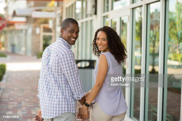 Portrait of smiling couple holding hands and looking at camera