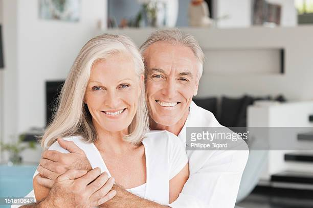 Portrait of smiling couple hugging in living room