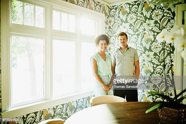 Portrait of smiling couple in dining room of home