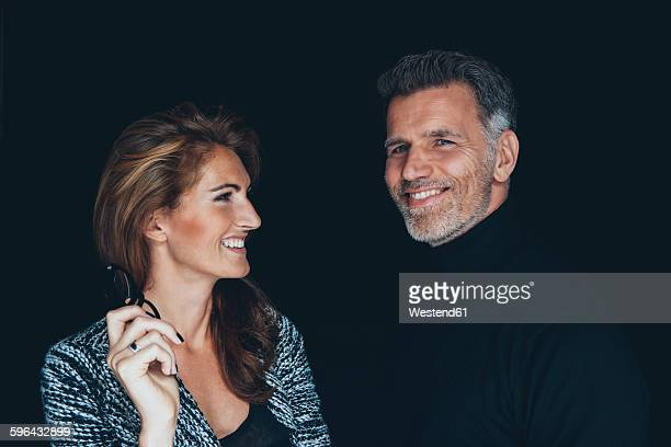 Portrait of smiling couple in front of black background