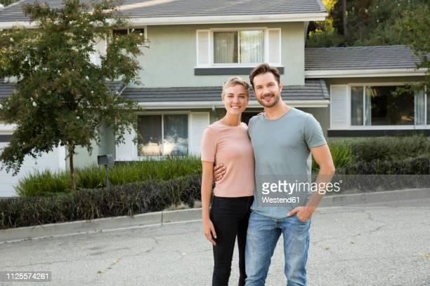 portrait of smiling couple in front of their home - eigenheim stock-fotos und bilder