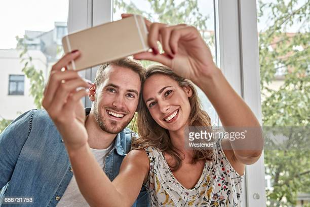 Portrait of smiling couple in front of window taking selfie with smartphone