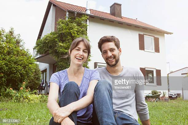 Portrait of smiling couple in garden in front of residential house