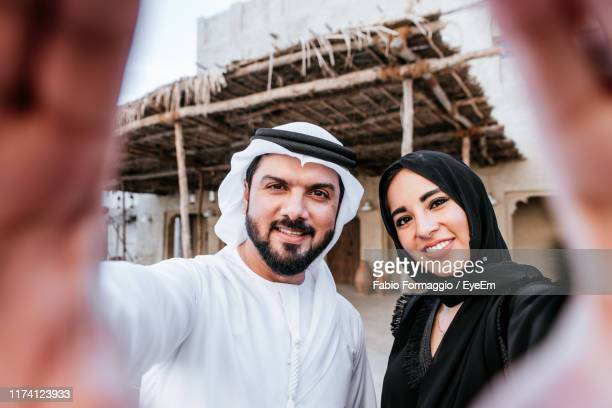 portrait of smiling couple making hand sign - hand sign stock pictures, royalty-free photos & images