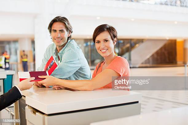 Portrait of smiling couple receiving tickets at airport check-in counter
