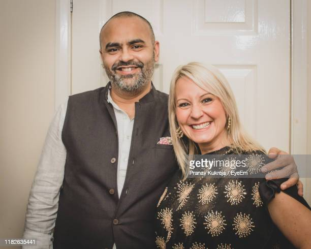 portrait of smiling couple standing at home - leicester stock pictures, royalty-free photos & images