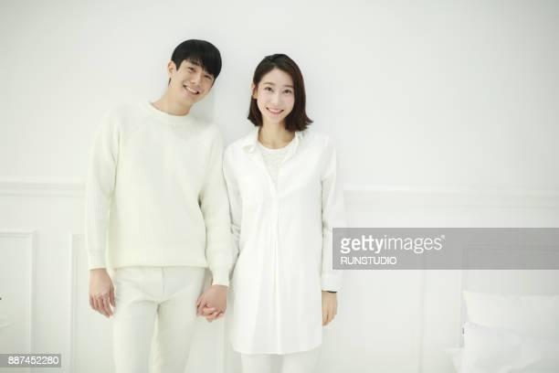 portrait of smiling couple standing in living room - 近く ストックフォトと画像