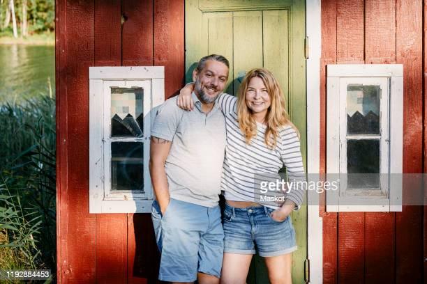 portrait of smiling couple standing with arms around against door at log cabin - relationship stockfoto's en -beelden