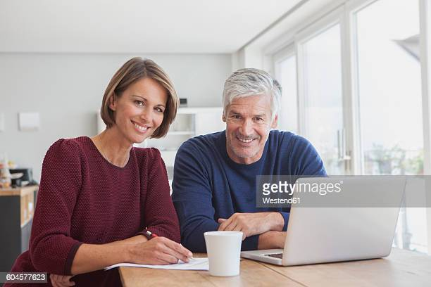 Portrait of smiling couple with laptop at home