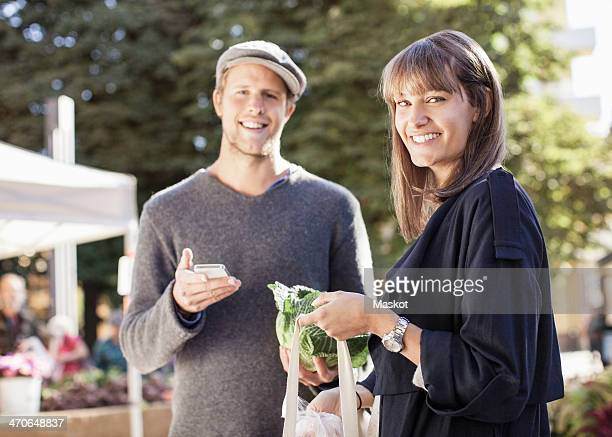 Portrait of smiling couple with mobile phone and groceries in market