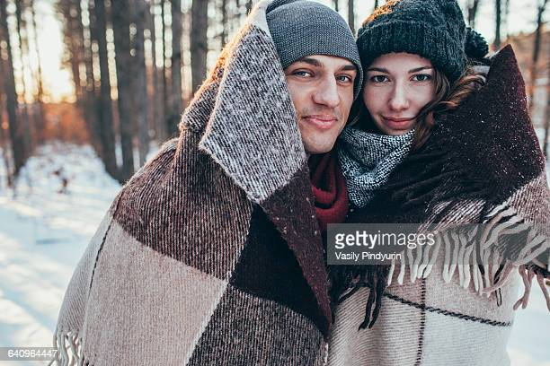 Portrait of smiling couple wrapped in blanket while standing on snow covered field