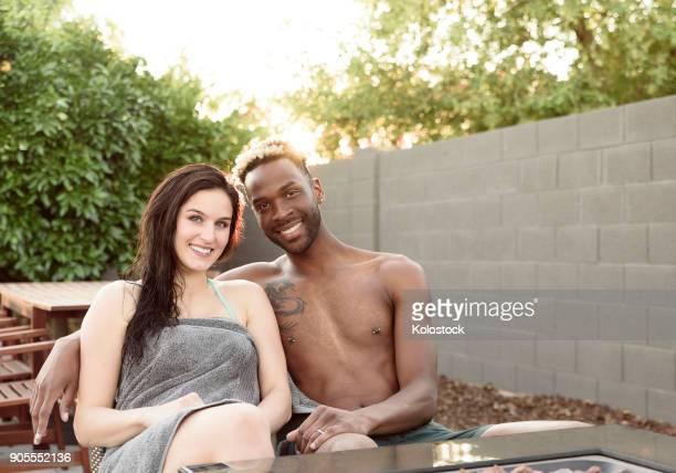 portrait of smiling couple wrapped in towels near fire pit - brustwarzen piercing stock-fotos und bilder