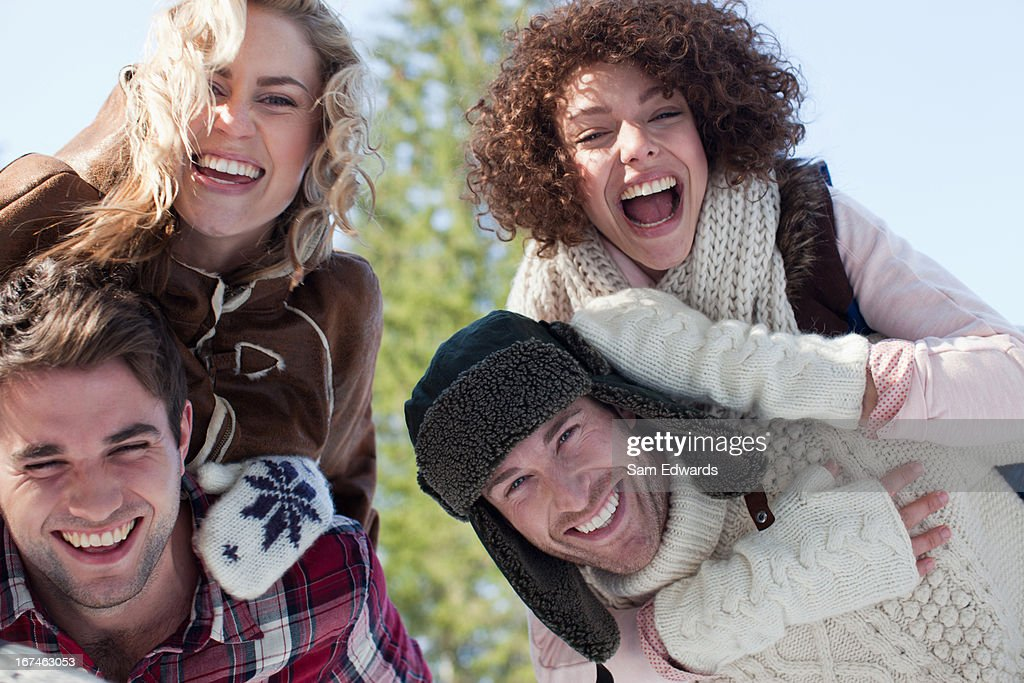 Portrait of smiling couples piggybacking : Stock Photo