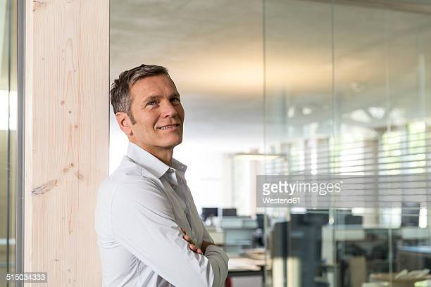 Portrait of smiling creative business man in front of office