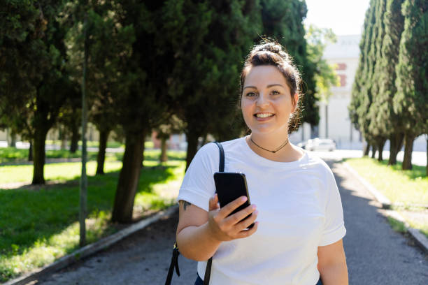 Portrait of smiling curvy young woman with mobile phone in a public park