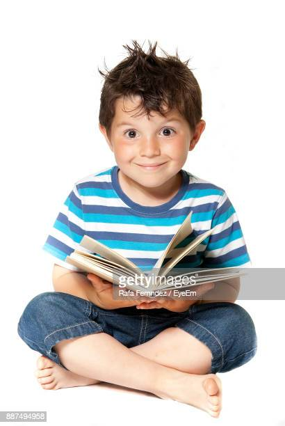Portrait Of Smiling Cute Boy Studying Against White Background