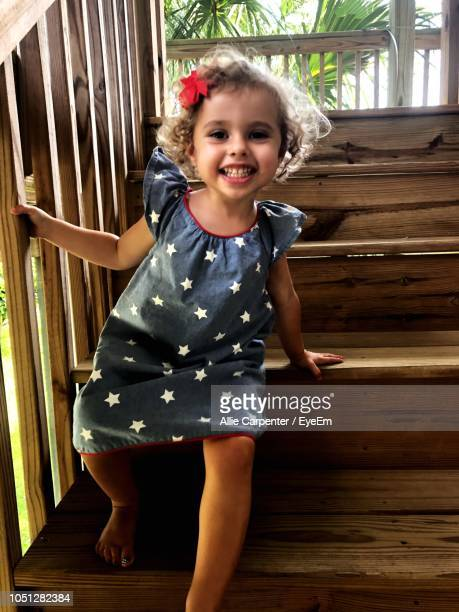 Portrait Of Smiling Cute Girl Sitting On Wooden Staircase