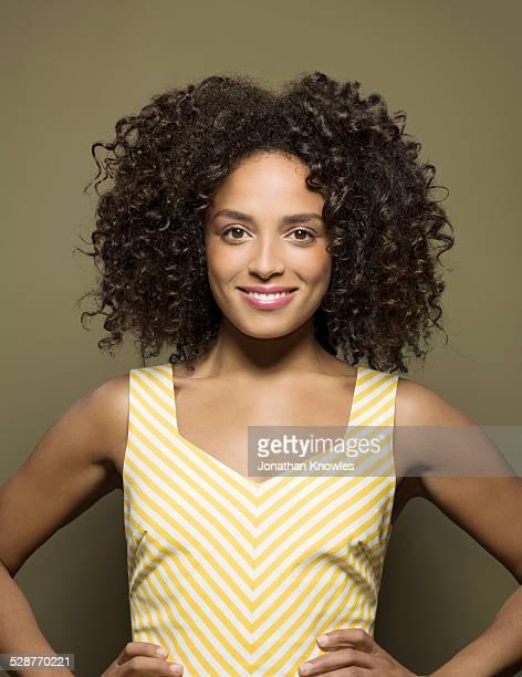 portrait of smiling dark skinned female - ricciolo foto e immagini stock