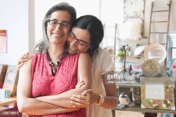 Portrait of smiling daughter hugging store owner mother