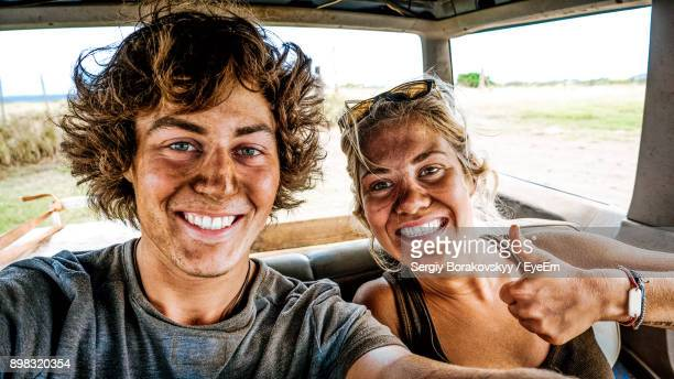 Portrait Of Smiling Dirty Friends Sitting In Car