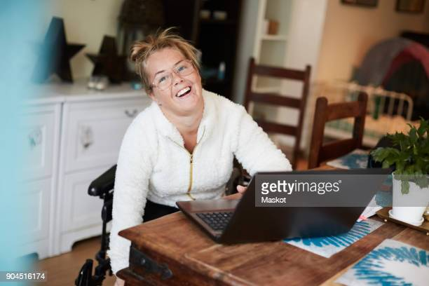Portrait of smiling disabled woman using laptop at table in house