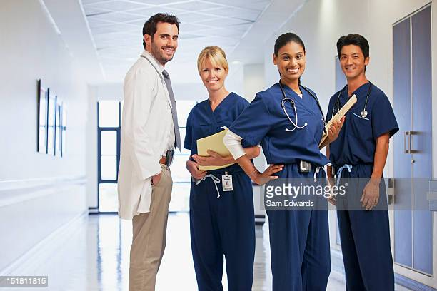 Portrait of smiling doctor and nurses in hospital corridor