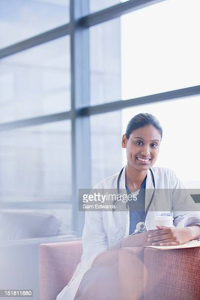 Retrato de la sonriente médico bebiendo café