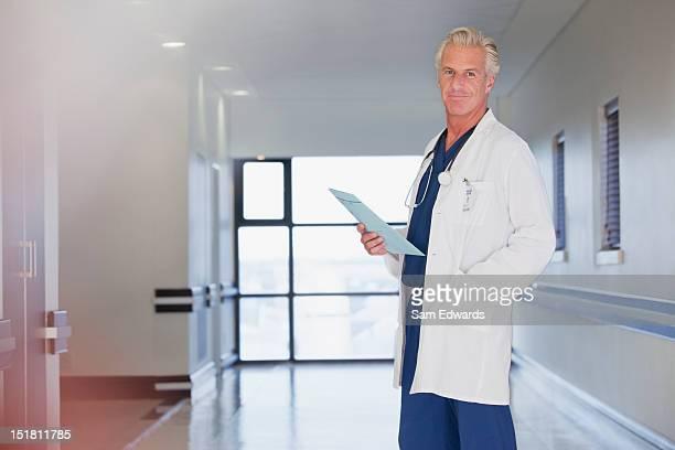 porträt von lächelnd arzt hält krankenakte in hospital, co - hände in den taschen stock-fotos und bilder