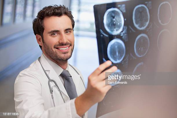 Portrait of smiling doctor holding x-ray in hospital corridor