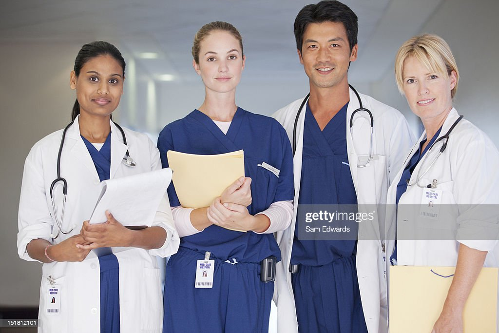 Portrait of smiling doctors and nurse holding medical records in hospital corridor : Stock Photo
