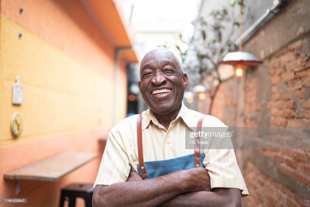 カメラを見て笑顔の高齢ウェイターの肖像 : ストックフォト