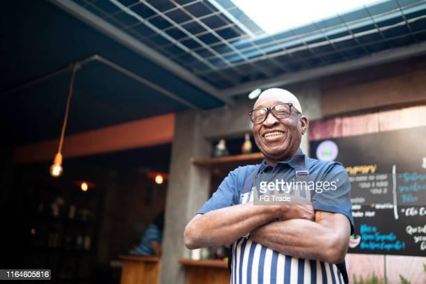 retrato do empregado de mesa idoso de sorriso que olha a câmera - dono - fotografias e filmes do acervo