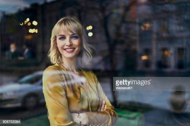 Portrait of smiling elegant woman behind windowpane