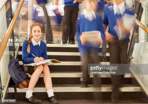 Portrait of smiling elementary school girl sitting on steps in school