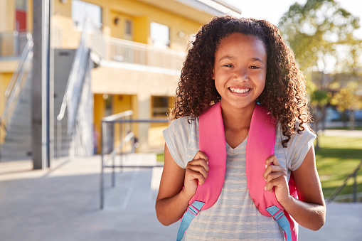 Portrait of smiling elementary school girl with her backpack 1045331466