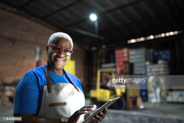 portrait of smiling employee using digital tablet at warehouse - pardo brazilian stock pictures, royalty-free photos & images