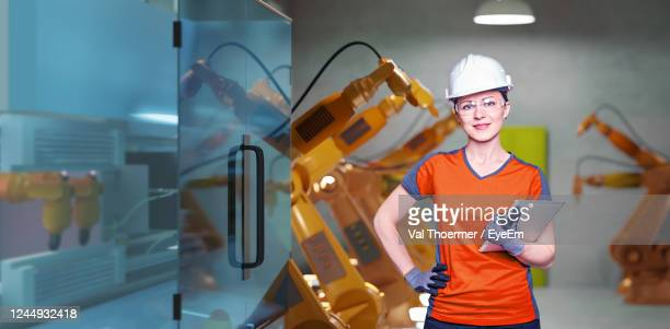 portrait of smiling engineer holding digital tablet in office - val thoermer stock-fotos und bilder