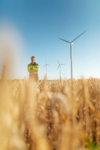 Portrait of smiling engineer standing in a field at a wind farm - gettyimageskorea