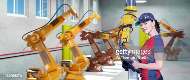 portrait of smiling engineer using equipment at factory - val thoermer stock-fotos und bilder