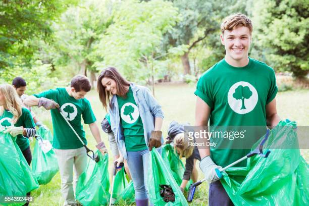 Portrait of smiling environmentalist volunteer picking up trash