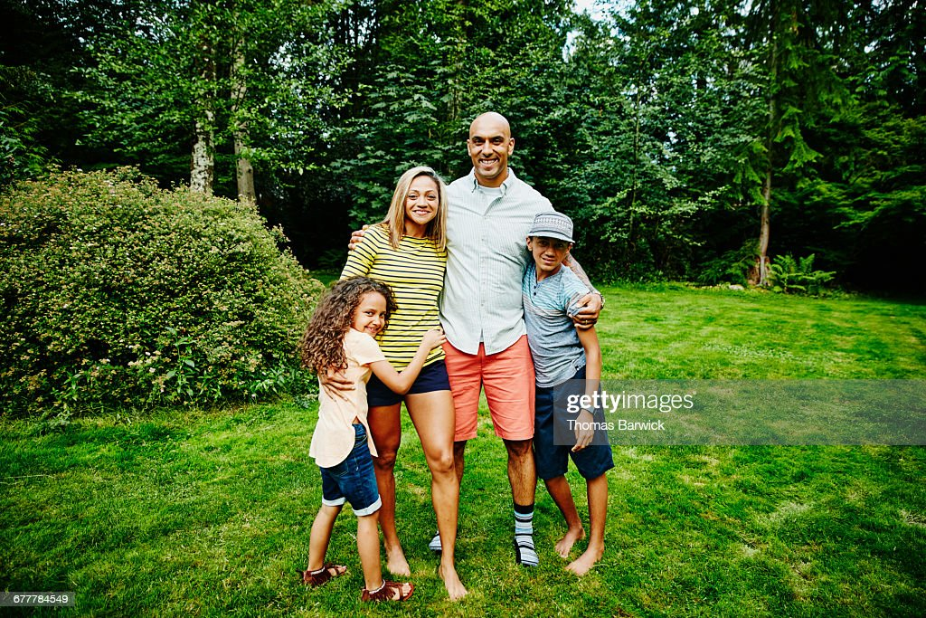 Portrait of smiling family embracing in backyard : Stock Photo