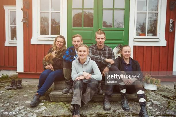 Portrait of smiling family sitting at entrance of house